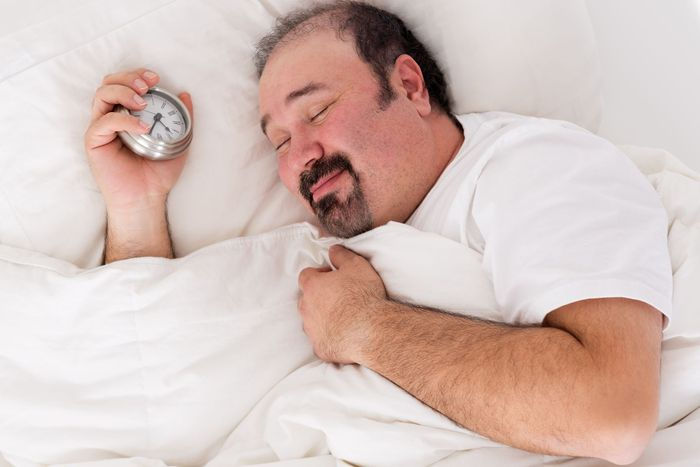 Man lying in bed smiling in contentment after a good nights sleep feeling relaxed and refreshed as he struggles to wake up in the morning with his alarm clock in his hand